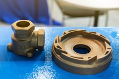 Industrial casting parts vane pump or propeller blades and water joint Brass fittings on blue table.  stock images