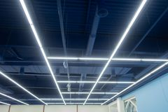 Industrial ceiling painted neutral blue. Lamps are placed in the form of longitudinal and transverse lines. Creative ceiling solut stock image