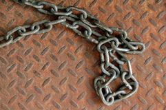 Industrial chain. Large industrial chain lying on old rusty diamond plate royalty free stock images