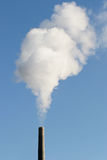 Industrial chimney. With smoke against blue sky, vertical version with copyspace Stock Image