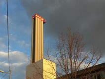 Industrial chimney in front of partly blue, partly polluted sky with dark clouds stock photography