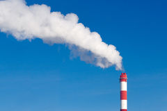 Industrial chimney with lot of smoke. On a blue sky stock images