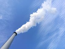 Industrial chimney producing white smoke. Industrial chimney discharging a white smoke into the atmosphere Royalty Free Stock Photos