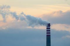 Industrial chimney smoke. Dirty smoke on a background sky, ecological problems. A large industrial smokestack sends smoke up into a cloudy sky Stock Photography
