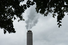 Industrial chimney with smoke with tree in the front Royalty Free Stock Photo