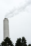 Industrial chimney with smoke with tree in the front Stock Image