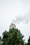 Industrial chimney with smoke with tree in the front stock images