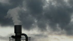 Industrial chimney or stack exhaling pollution smoke in industrial plant at cloudy day at sunset. Chimney or stack in plant industrial exhaling pollution smoke stock footage