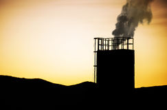 Industrial chimney in sunset. With smoke Royalty Free Stock Photos