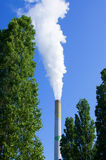 Industrial chimney between trees Royalty Free Stock Images