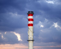 Industrial chimneys on cloudy sky at sunset Stock Images