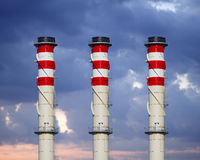 Industrial chimneys on cloudy sky at sunset Stock Image