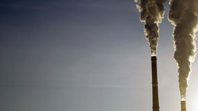Industrial chimneys emits toxic pollutants into the sky polluting the environment. Royalty Free Stock Photo
