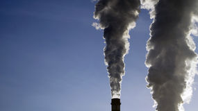 Industrial chimneys emits toxic pollutants into the sky polluting the environment. Stock Photo