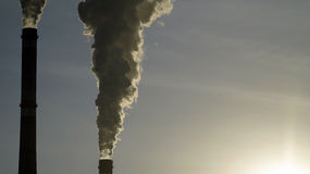 Industrial chimneys emits toxic pollutants into the sky polluting the environment. Royalty Free Stock Images