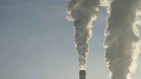 Industrial chimneys emits toxic pollutants into the sky polluting the environment. Royalty Free Stock Image