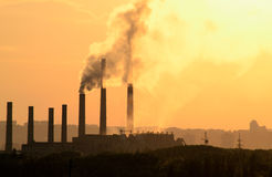 Industrial chimneys. Industrial plant on a background of orange sky Stock Photo