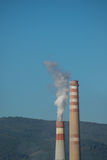 Industrial chimneys with white smoke on blue sky. And forest in the background Royalty Free Stock Photos