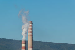 Industrial chimneys with white smoke on blue sky. And forest in the background Royalty Free Stock Images