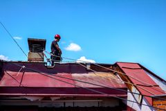 Industrial climber is bounding his ropes to the chimney made of. Industrial climber, alpinist, is adjusting climbing gear, preparing safety ropes Stock Photos