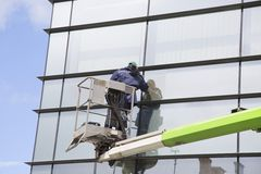 Industrial climber with cleaning equipment, washes windows. Industrial climber with cleaning equipment on the tower washes windows in office building stock image
