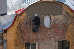 Industrial climber restores wall on the building. Royalty Free Stock Photos