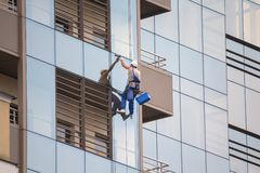 Industrial climber wash the windows of modern skyscraper stock photography