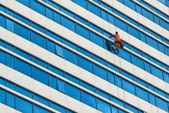 Industrial climber wash the windows of skyscraper. royalty free stock photo