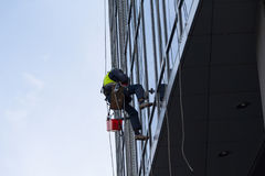 Industrial climber washes the facade of a multistory building Stock Photo