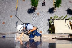 Industrial climber is washing, cleaning facade of a modern office building. Above view on young man, industrial climber at work, he washing building facade stock images