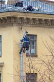 Industrial climbers repair a drainpipe on the wall of a residential building royalty free stock photography