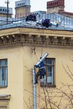 Industrial climbers repair a drainpipe on the wall of a residential building stock photo