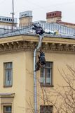 Industrial climbers repair a drainpipe on the wall of a residential building royalty free stock image