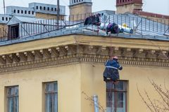 Industrial climbers repair a drainpipe on the wall of a residential building stock image