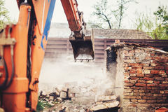 industrial excavator using scoop for demolishing old house and ruins Royalty Free Stock Photos