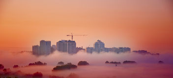 Industrial clouds. High-rise buildings in red sunrise clouds Royalty Free Stock Photography