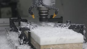 Industrial lathe milling machine CNC. Industrial CNC Machine cutting out the detail out of white plastic material stock footage