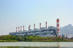 Industrial coal power plant with smokestacks and wetland or reservoir royalty free stock photos