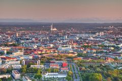 Industrial and commercial buildings in outskirts Munich Germany. Aerial view of modern European city outskirts in evening sunlight with tower blocks, chimneys royalty free stock images