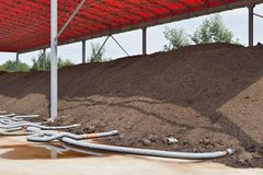 Industrial compost. Heap with forced aeration pipes royalty free stock photography