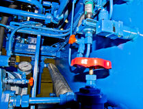 Industrial compressor pipework. A blue industrial compressor detail showing pipework and valves royalty free stock image
