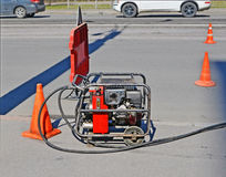 Industrial compressor on repaired road. Industrial compressor on road during repairs. Site is fenced with warning road sign and signal cones royalty free stock photo