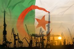 Industrial concept with Algeria flag at sunset. Silhouette of container harbor royalty free stock image