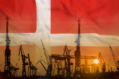 Industrial concept with Denmark flag at sunset. Silhouette of container harbor Stock Photo