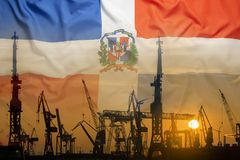 Industrial concept with Dominican Republic flag at sunset. Silhouette of container harbor stock photo