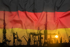 Industrial concept with Germany flag at sunset. Silhouette of container harbor Royalty Free Stock Image