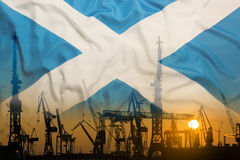 Industrial concept with Scotland flag at sunset. Silhouette of container harbor royalty free stock photo