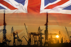 Industrial concept with United Kingdom flag at sunset. Silhouette of container harbor Stock Photo