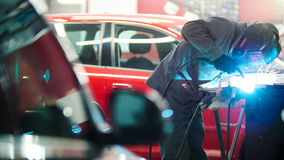 Industrial concept: worker in helmet repair detail in car auto service Royalty Free Stock Photography