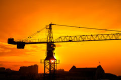 Industrial construction crane and buildings silhouettes over sun at sunrise Royalty Free Stock Photo